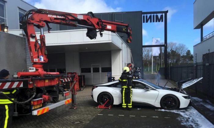 Dutch fire crews put a smoking BMW i8 into a huge vat of water in Brabant province, Netherlands, on March 25, 2019.(Brandweer Midden- en West-Brabant)
