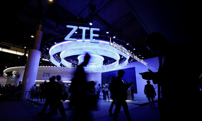 People walk next to ZTE booth at the Mobile World Congress in Barcelona, Spain on Feb. 25, 2019. (Rafael Marchante/Reuters)