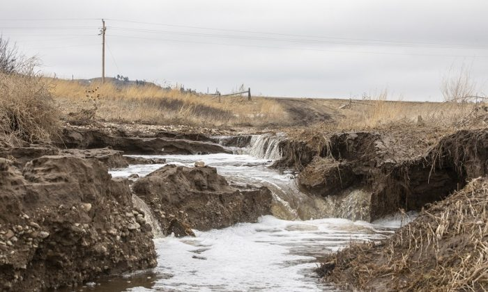 Following spring flooding water gushes along the driveway to Betty Lou Brave Heart's home near Porcupine, S.D., on the Pine Ridge Indian Reservation on March 25, 2019. (Ryan Hermens/Rapid City Journal via AP)