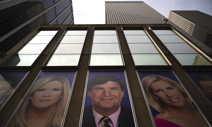 Advertisements featuring Fox News personalities, including Tucker Carlson (C), adorn the front of the News Corporation building, March 13, 2019 in New York City.  Drew Angerer/Getty Images