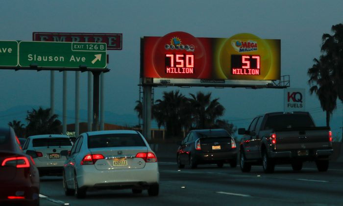 A highway billboard promoting the current Powerball jackpot lottery  reaches out to commuters in Los Angeles, Calif., on March 26, 2019. (Mike Blake/Reuters)