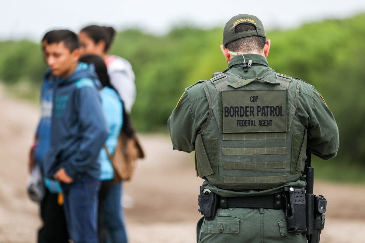 A Border Patrol agent apprehends illegal aliens who have just crossed the Rio Grande from Mexico into Penitas, Texas