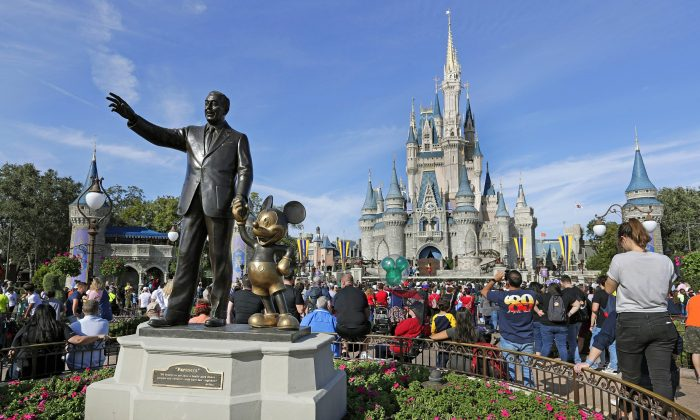 Guests watch a show near a statue of Walt Disney and Micky Mouse in front of the Cinderella Castle at the Magic Kingdom at Walt Disney World in Lake Buena Vista, Fla., on Jan. 9, 2019. (John Raoux/AP Photo)