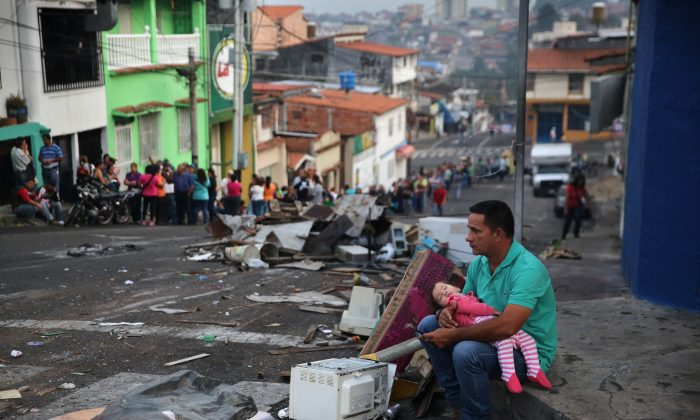 A father and daughter rest while someone holds their place before sunrise in a long line to buy basic foodstuffs at a supermarket on March 8, 2014 in San Cristobal, the capital of Tachira state, Venezuela.  John Moore/Getty Images