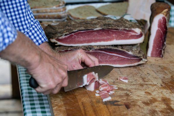 Man cutting Italian speck by hand