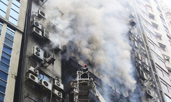 A firefighter works to douse a fire in a multi-storied office building at Banani, in Dhaka, Bangladesh, on March 28, 2019. (Mahmud Hossain Opu, File/AP Photo)
