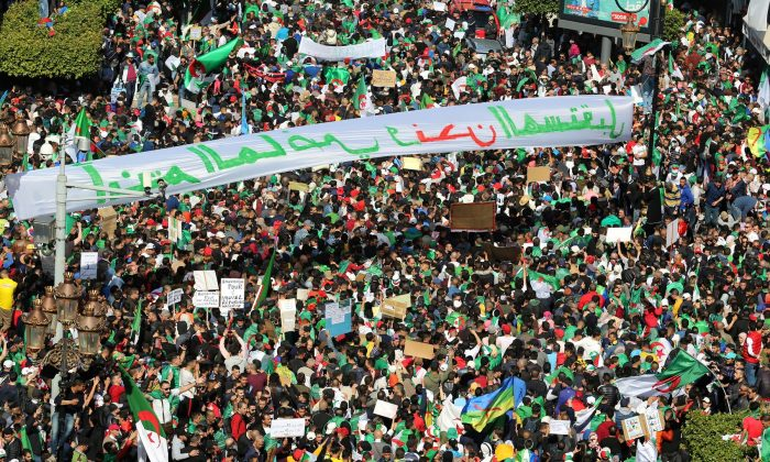 People carry national flags and banners during a protest to demand the resignation of President Abdelaziz Bouteflika, in Algiers, Algeria on March 29, 2019. (Ramzi Boudina/Reuters)