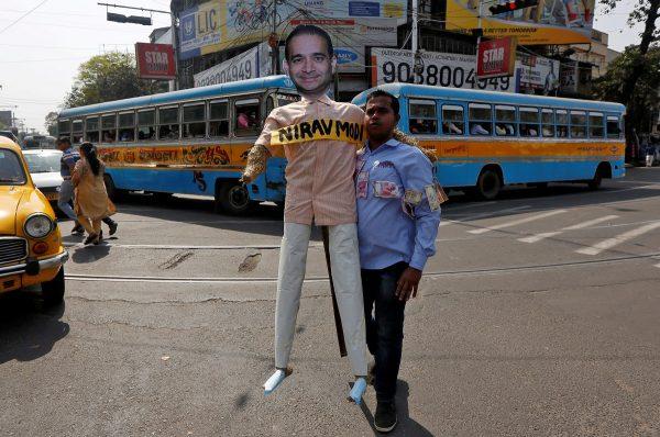 A demonstrator holds an effigy depicting billionaire jeweller Nirav Modi