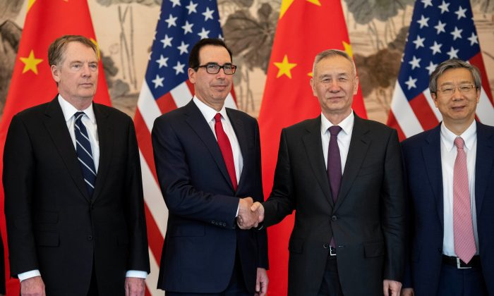China's Vice Premier Liu He shakes hands with U.S. Treasury Secretary Steven Mnuchin as Yi Gang, governor of the People's Bank of China (PBC) and U.S. Trade Representative Robert Lighthizer stand next to them as they pose for a group photo at Diaoyutai State Guesthouse in Beijing on March 29, 2019. (Nicolas Asfouri/Pool via Reuters)