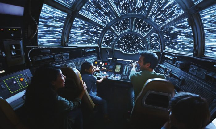 This rendering released by Disney and Lucasfilm shows people on the planned Inside Millennium Falcon: Smugglers Run attraction, part of Star Wars: Galaxy's Edge a 14-acre area set to open this summer at the Disneyland Resort in Anaheim, California, then in the fall at Disney's Hollywood Studios in Orlando, Florida. (Disney Parks/Lucasfilm via AP)