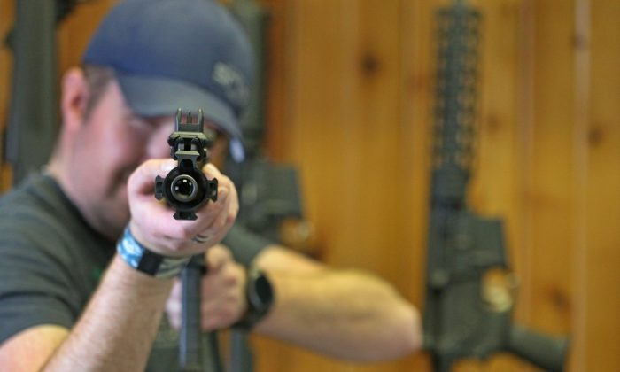 An AR-15 was used in the Marjory Stoneman Douglas High School shooting in Parkland, Fla. Dordon Brack, aims a semi-automatic AR-15 that is for sale at Good Guys Guns & Range on Feb. 15, 2018, in Orem, Utah. (George Frey/Getty Images)