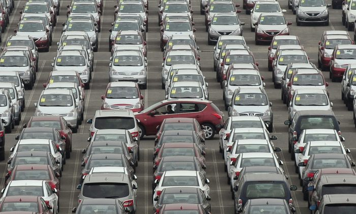 A man drives a red car past a parking lot where large numbers of newly manufactured cars are parked at Dayaowan port of Dalian, Liaoning Province on June 10, 2012. (Reuters)