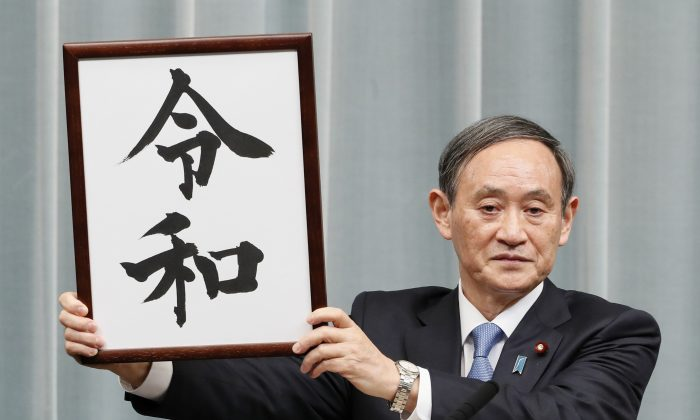 """Japan's Chief Cabinet Secretary Yoshihide Suga unveils the new era name """"Reiwa"""" at a news conference in Tokyo, Japan, on April 1, 2019.  (Kyodo/via Reuters)"""