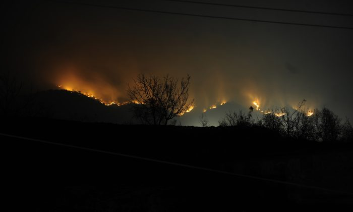 A forest blaze rages on in a remote mountainous region of Qinhuangdao, northeast China's Hebei Province on April 13, 2011. The forest fire destroyed over 133 hectares of forest, according to local authorities. (STR/AFP/Getty Images)