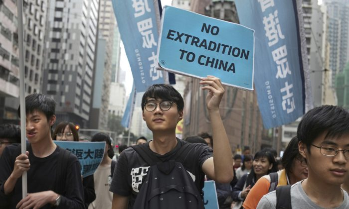 Protesters raise placards and flags during a march against an extradition law as they head toward government headquarters in Hong Kong on March 31, 2019. Thousands of people protest against the proposed changes to the Hong Kong's extradition laws that could see people sent for trial in mainland China, according to government radio. (Vincent Yu/AP Photo)