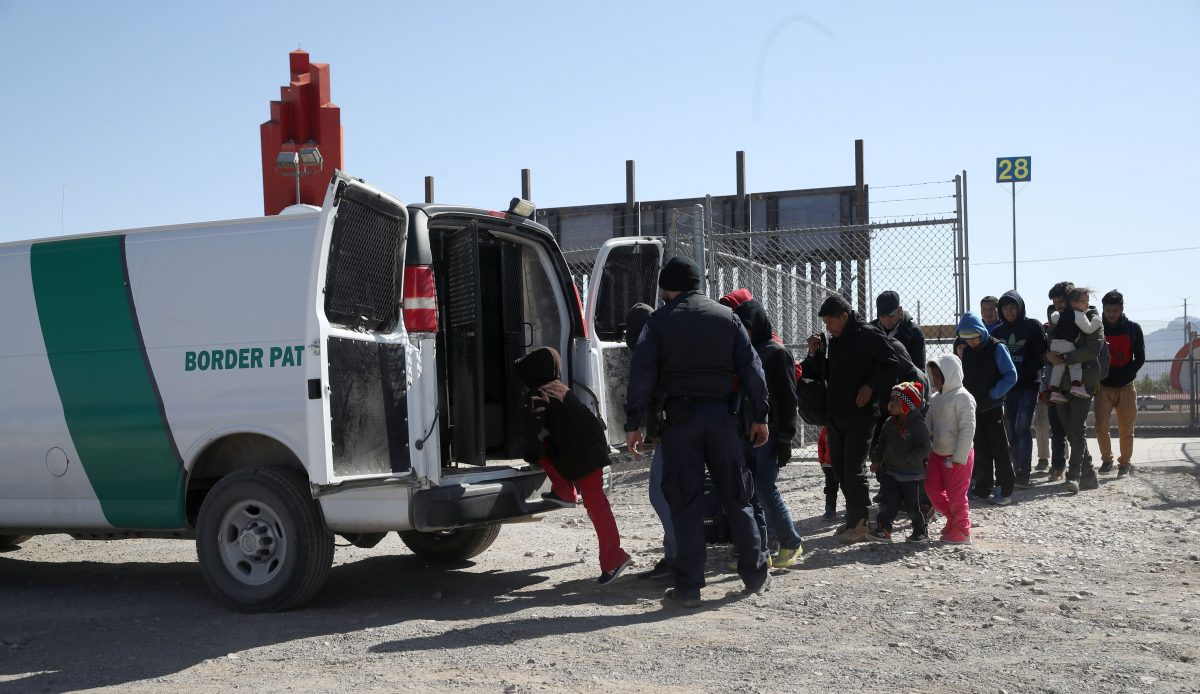 A Border Patrol agent loads detained migrants into a van at the border of the United States and Mexico in El Paso