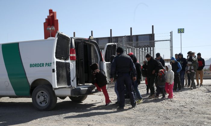 A Border Patrol agent loads detained migrants into a van at the border of the United States and Mexico in El Paso, Tex., on March 31, 2019. (Justin Sullivan/Getty Images)