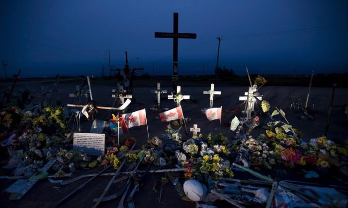 A memorial made of hockey sticks, crosses, and Canadian flags is seen at the crash site of the Humboldt Broncos hockey team near Tisdale, Sask. (Jonathan Hayward/The Canadian Press)