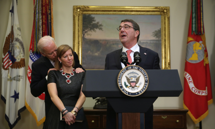 Ashton Carter (R) makes remarks after he was sworn in as secretary of defense as his wife Stephanie (2nd L) and  Vice President Joe Biden (L) listen, on Feb. 17, 2015, in the Roosevelt Room of the White House. (Alex Wong/Getty Images)