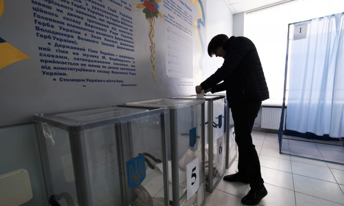 A voter in Ukraine's eastern city of Kharkiv casts a ballot during the first round of the country's presidential election on March 31, 2019. (Chris Collison for The Epoch Times)