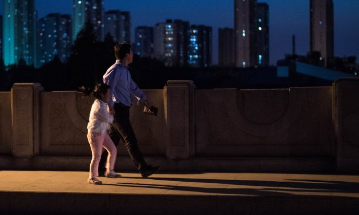A man and a girl walking on a bridge in Shanghai, China. (Johannes Eisele/AFP/Getty Images)