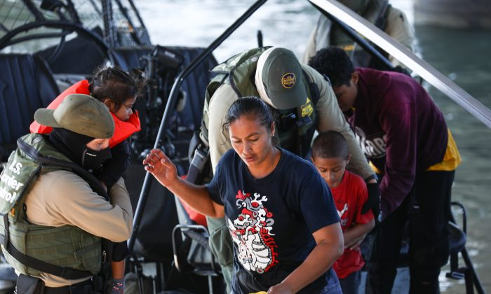 Illegal border crossers are rescued by agents on a U.S. Customs and Border Protection boat after they got stuck halfway across the Rio Grande from Mexico into Eagle Pass, Texas, on Feb. 16, 2019. (Charlotte Cuthbertson/The Epoch Times)