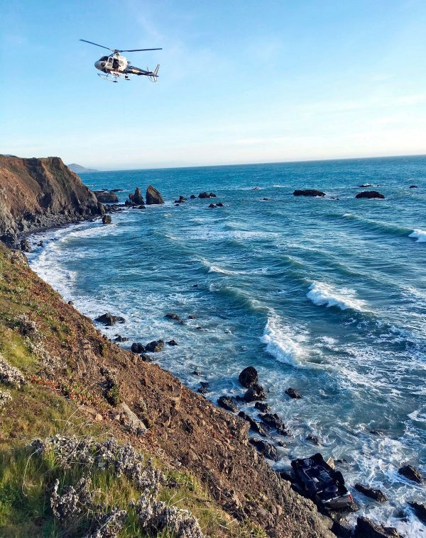 A helicopter hovers over steep coastal cliffs near Mendocino