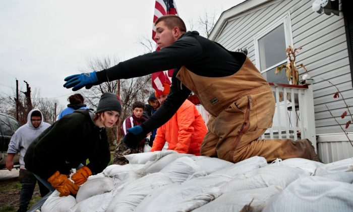 People cleaning up after flood. (Robert Cohen/St. Louis Post-Dispatch via AP)