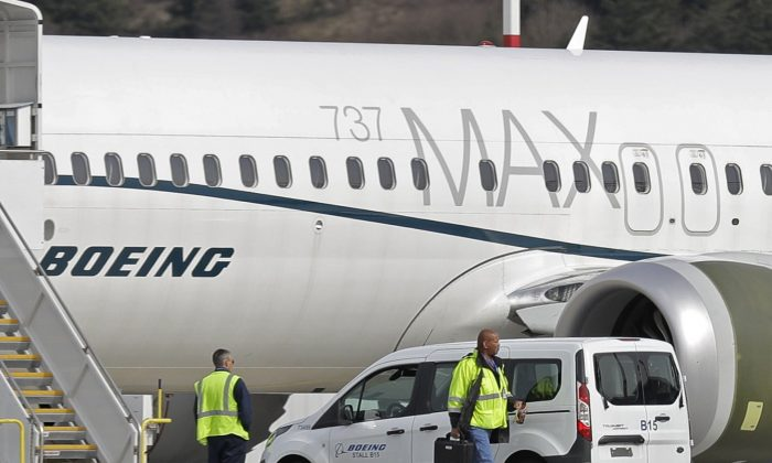 Workers walk next to a Boeing 737 MAX 8 airplane parked at Boeing Field, in Seattle, on March 14, 2019. (Ted S. Warren/File via AP)