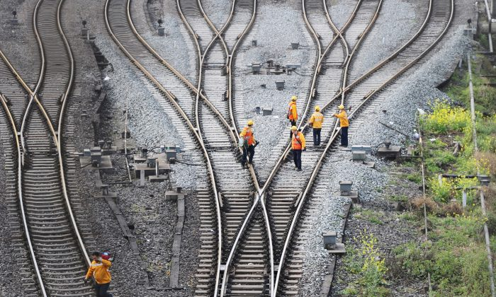 Workers inspect railway tracks, which serve as a part of the Belt and Road Initiative freight rail route linking Chongqing to Duisburg, at the Dazhou railway station in Sichuan Province, China, on March 14, 2019. (Reuters)