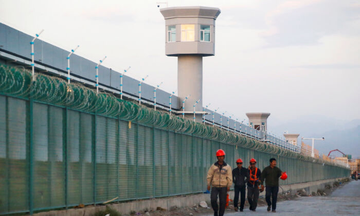 Workers walk by the perimeter fence of what is officially known as a vocational skills education center in Dabancheng in Xinjiang Uyghur Autonomous Region, China on Sept. 4, 2018. (Thomas Peter/Reuters)