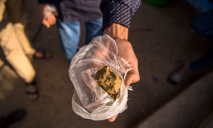 A farmer displays a piece of cannabis resin (hashish) near the town of Ketama in Morocco's northern Rif region on Sept. 13, 2017. (Fadel Senna/AFP)