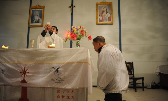 A priest prepares to offer holy communion during a Christmas Eve mass at a house church in Pengzhou City, Sichuan Province, China, on December 24, 2008. (China Photos/Getty Images)