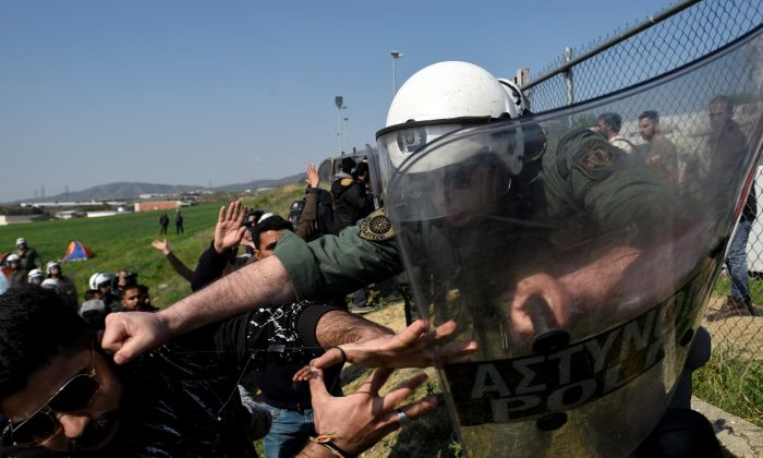 A riot police officer hits a migrant as migrants and refugees argue with riot police officers next to a camp in the town of Diavata in northern Greece, on April 4, 2019. (Alexandros Avramidis/Reuters)