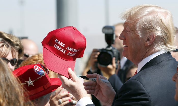 """President Donald Trump hands a signed """"Make America Great Again,"""" hat back to a supporter in Reno, Nev., on Aug. 23, 2017. (Alex Brandon/AP Photo)"""
