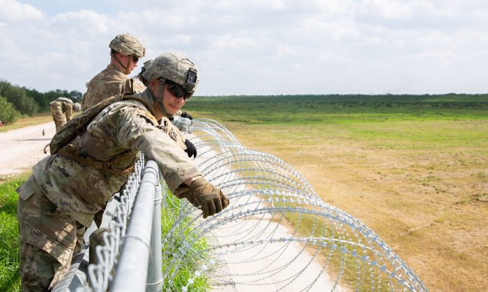 The U.S. military installs concertina wire on the existing levee wall behind Granjeno, Hidalgo County, Texas, just north of the U.S.–Mexico border on Nov. 7, 2018. (Samira Bouaou/The Epoch Times)