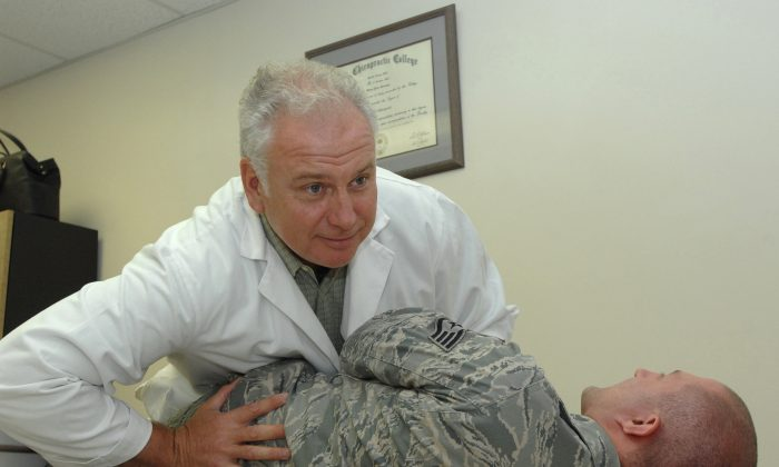 Dr. Brian Brennan performs a lower back alignment for Staff Sgt. Robert Barnett Aug. 9, 2011, in the Wilford Hall Medical Center Chiropractic Clinic, Lackland Air Force Base, Texas. Back alignments can help relieve lower back pain. (U.S. Air Force photo by Audrey Acuna)