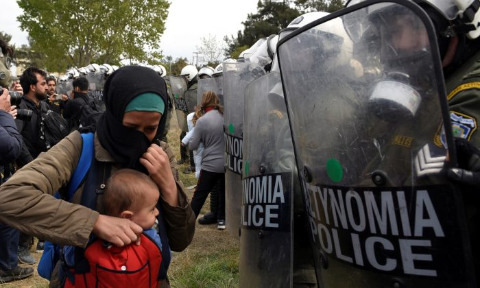 A woman holds her baby in front of riot police as migrants and refugees, who say that they seek to travel onward to northern Europe, walk away from a camp near the town of Diavata in northern Greece, on April 5, 2019. (Alexandros Avramidis/Reuters)