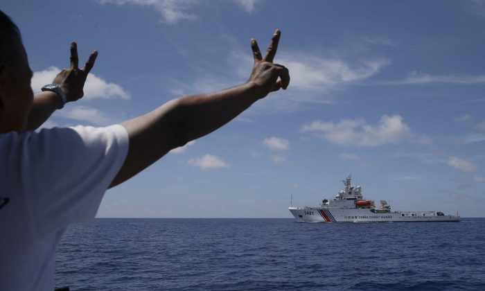 A China Coast Guard vessel attempts to block a Philippine government vessel as the latter tries to enter the China Second Thomas Disputed Shoals, locally known as Ayungin Shoal, to orate Philippine troops and resupply provisions on March 29, 2014. (Bullit Marquez/AP)