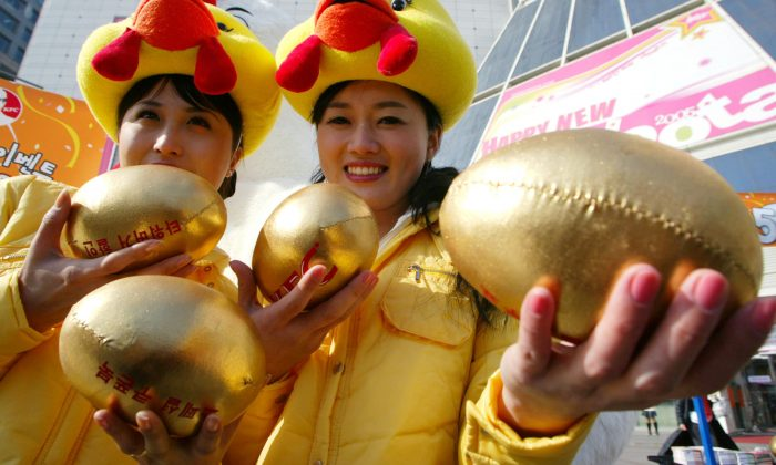 Women holding stuffed golden eggs. (Chung Sung-Jun/Getty Images)