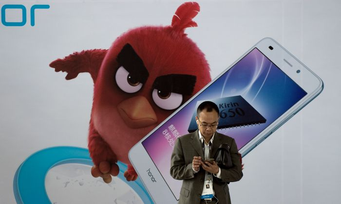 A man uses his smartphone during the Global Mobile Internet Conference (GMIC) at the National Convention Centre in Beijing on April 28, 2016. (NICOLAS ASFOURI/AFP/Getty Images)