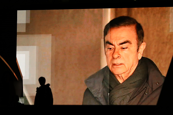 TOKYO, JAPAN - APRIL 04: Pedestrians walk past a big screen showing images of former Nissan Motor Co. Chairman Carlos Ghosn in a news program on April 4, 2019 in Tokyo, Japan. Ghosn, a veteran of the auto industry, was re-arrested on Thursday for financial misconduct. (Photo by Takashi Aoyama/Getty Images)