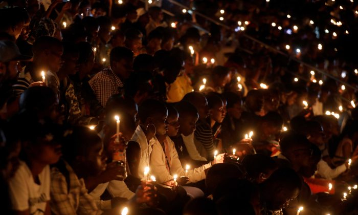 Participants hold candles while holding a night vigil during a commemoration ceremony marking the 25th anniversary of the Rwandan genocide, at the Amahoro stadium in Kigali, Rwanda April 7, 2019. REUTERS/Baz Ratner