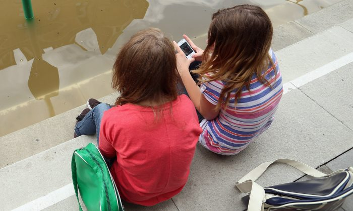 Two girls sit and discuss apps on their phones. (Sean Gallup/Getty Images)