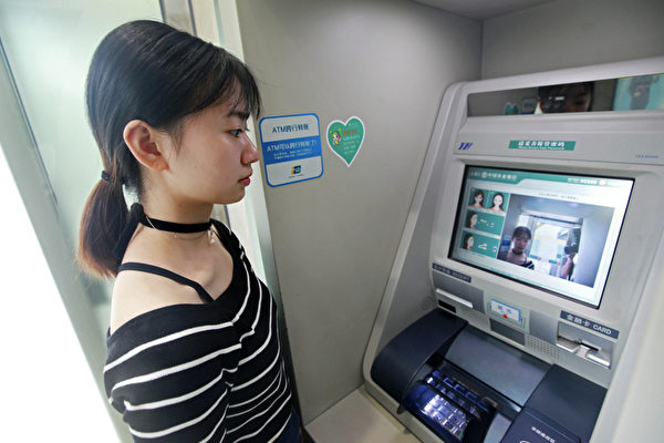 A customer withdraws money from an ATM machine using a facial recognition feature at the Agricultural Bank of China. (The Epoch Times)