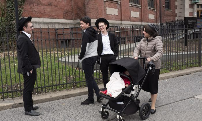 A woman passes a group of boys in the Williamsburg section of Brooklyn, New York on April 9, 2019.  AP Photo/Mark Lennihan