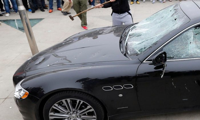A rich business owner's Maserati being attacked by sledge hammers. (STR/AFP/Getty Images)