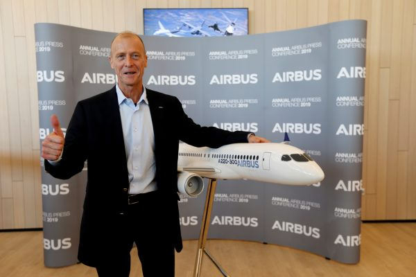Airbus Chief Executive Tom Enders poses with a A220-300 Airbus replica
