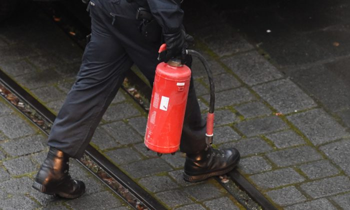 A police officer carrying a fire extinguisher. (Odd Andersen/AFP/Getty Images)