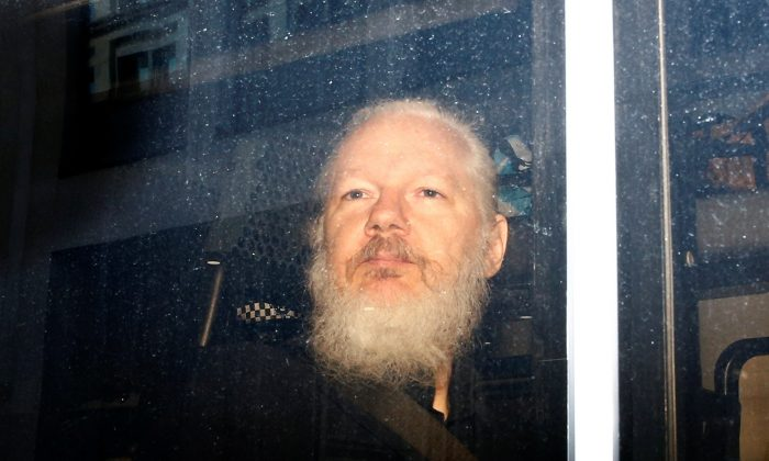 WikiLeaks founder Julian Assange is seen in a police van, after he was arrested by British police, in London, Britain April 11, 2019. (Henry Nicholls/Reuters)